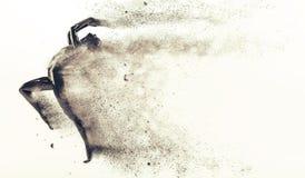 Abstrakt svart plast- människokroppskyltdocka med spridningpartiklar över vit bakgrund Den handlingspring och banhoppningen poser Royaltyfri Bild
