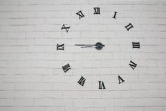 Abstrakt tegelstenvägg med klockanummer Arkivbilder