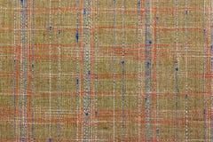 Abstrakt textur av brunt bomullstyg med vit, rött och blålinjen Bakgrund för naturligt tyg Royaltyfri Foto