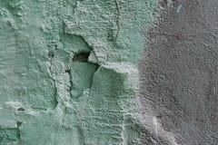 Abstrakt textur av en gammal bruten vägg med en ojämn yttersida: på som lämnas en försiktig grön målarfärg med gropar och på rätt Arkivfoto