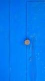 Abstrakt textur av en rostig metalldörr som täckas i blått, målar med det runda handtaget Royaltyfri Fotografi