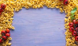 abstrakt textur för bakgrundsmatpasta Flera typer av torr pasta med grönsaker och kryddan på en trätabell Fritt avstånd för text  Fotografering för Bildbyråer
