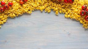 abstrakt textur för bakgrundsmatpasta Flera typer av torr pasta med grönsaker och kryddan på en trätabell Fritt avstånd för text  Arkivfoto