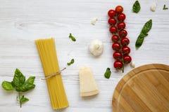 abstrakt textur för bakgrundsmatpasta Spagetti med tomater, ostparmesan och basilika på den vita trätabellen Arkivfoton