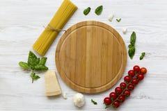 abstrakt textur för bakgrundsmatpasta Spagetti med tomater, ostparmesan och basilika, träbräde i mitten Royaltyfri Fotografi