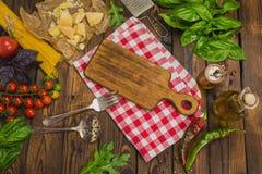 abstrakt textur för bakgrundsmatpasta Torr spagetti med grönsaker och örter på en w Fotografering för Bildbyråer
