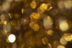 Abstrakt textur med guld blänker att skimra i solen lampa Arkivfoto