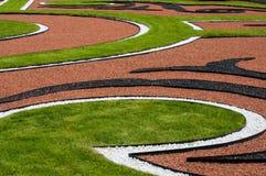 Abstrakt utomhus- sammansättning av kurvor i gräsmattan Arkivfoton