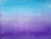 Abstrakt vattenfärglutning med blå och violett färg på grovt papper arkivfoton