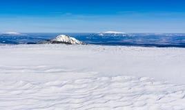 Abstrakt vision av havet i bergen Snöa som en sandig strand, och maxima dyker upp öar från havet Royaltyfria Bilder