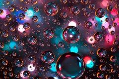Abstrakta bakgrundstexturdroppar av vatten och konst tänder på glas Fotografering för Bildbyråer