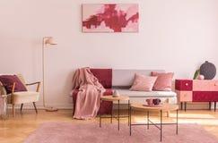 Abstrakta burgundy och pastellfärgad rosa målning på den tomma vita väggen av trendig vardagsrum som är inre med den flotta fåtöl royaltyfria bilder