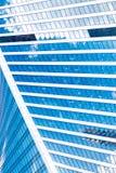 Abstrakta skyskrapor med reflexion i blå himmel för fönster, vitmoln och sol att glo Royaltyfri Bild