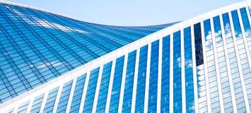 Abstrakta skyskrapor med reflexion i blå himmel för fönster, vitmoln och sol att glo Royaltyfria Bilder