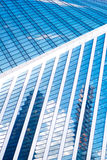 Abstrakta skyskrapor med reflexion i blå himmel för fönster, vitmoln och sol att glo Royaltyfri Foto