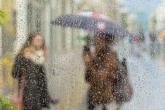 Abstrakta suddiga konturer av folk med paraplyer på regnig dag i stad, två flickor som ses till och med regndroppar på fönster Royaltyfria Foton