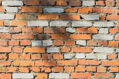 Abstrakte alte schädigende Backsteinmauer mit Sprüngen eines strukturierten Hintergrundes mit Raum für Text Stockbild