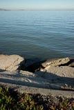Abstrakte Ansicht von defektem Concerete und von ruhiger Ozean-Bucht am späten Nachmittag Stockfotos