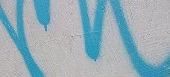 Abstrakte blaue Graffiti auf weißem Wandfahnenhintergrund stockbild