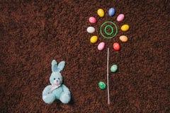 Abstrakte Blume mit farbigen Eiern auf dem Teppich ostern Flache Lage Lizenzfreies Stockbild