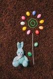 Abstrakte Blume mit farbigen Eiern auf dem Teppich ostern Flache Lage Lizenzfreie Stockbilder
