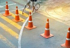 Abstrakte bunte Verkehrskegel und Fahrradmann auf dem Straßen-, Pastell- und buntenkonzept Lizenzfreie Stockbilder