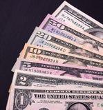 Abstrakte Dollarscheine von verschiedenen Bezeichnungen auf schwarzem Hintergrund Lizenzfreies Stockbild