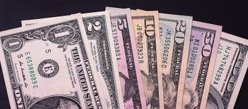 Abstrakte Dollarscheine von verschiedenen Bezeichnungen auf schwarzem Hintergrund Lizenzfreies Stockfoto
