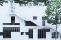 Abstrakte Fassade umgeben durch Bäume, Architekturhintergrund - verschiedene Formen der Grillfenster und Größen Lizenzfreies Stockbild