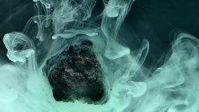 Abstrakte flüssige Tinte im Wasser mit Stein Lizenzfreie Stockbilder