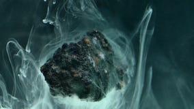 Abstrakte flüssige Tinte im Wasser mit Stein Lizenzfreie Stockfotos