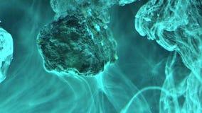 Abstrakte flüssige Tinte im Wasser mit Stein Lizenzfreie Stockfotografie