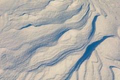 Abstrakte Formen und Muster des Winds im Schnee Stockbilder