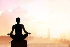 Abstrakte Frau, die auf Pastellfarbtonstadt im Sonnenuntergang meditiert lizenzfreies stockfoto