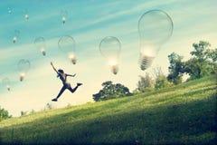 Abstrakte Frau, die für anziehende Glühlampe auf Feld des grünen Grases und der Blume läuft und springt Stockfotografie