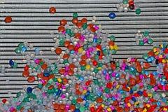 Abstrakte gelegentliche Farbkomponenten häufen auf Metallsilbernem Gitter, industrielle Verschiedenartigkeit, stockfotografie