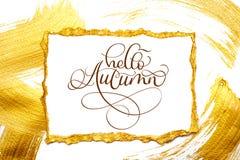 Abstrakte goldene Abstriche und Tag mit Papier auf weißem Hintergrund mit Text hallo Herbst Stockfotografie