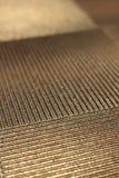 Abstrakte Goldmetalloberfläche mit diagonalen Linien in gegenüberliegenden Richtungen Stockfotografie