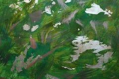 Abstrakte Hand, die grünen Hintergrund mit Goldacrylpinselstrichen zeichnet stockfotografie