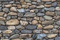 Abstrakte Hintergrundbeschaffenheit der Steinwand handgemacht von den Flusssteinen von verschiedenen Größen und von Formen von Gr Lizenzfreies Stockbild