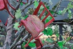 Abstrakte Installation: Schemel, der aus einem Baum heraus wächst Lizenzfreies Stockfoto