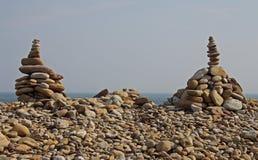 Abstrakte Kiesel-und Felsen-Skulpturen auf dem Strand Stockfotos