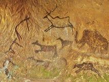 Abstrakte Kinderkunst in der Sandsteinhöhle. Schwarze Kohlenstofffarbe der Menschenjagd auf Sandsteinwand Lizenzfreie Stockbilder