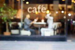 Abstrakte Leute im Kaffeestube- und Textcafé vor Spiegel-, Weiche- und Unschärfekonzept Lizenzfreies Stockbild