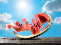 abstrakte lustige Wassermelonenscheibe auf hölzerner Tabelle mit Sonnenhimmel summe Stockfoto