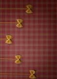 Abstrakte Nahrungsmittelbeschaffenheit Fliege und Spaghettis auf roter quadratischer Tischdecke Flache Lage Beschneidungspfad ein Lizenzfreie Stockbilder