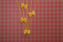 Abstrakte Nahrungsmittelbeschaffenheit Trockenes Vollkorn-farfalle und Spaghettis auf roter quadratischer Tischdecke Flache Lage  Lizenzfreies Stockbild