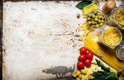 Abstrakte Nahrungsmittelbeschaffenheit Viele verschiedenen Teigwaren, Oliven, Tomaten, Öl und Kräuter Stockfotos