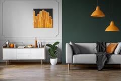 Abstrakte orange Malerei auf der grauen Wand des stilvollen Wohnzimmers Innen mit weißem Holzmöbel und grauer Couch stockfotografie