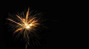 Abstrakte pyrotechnische glühende Explosion auf schwarzem Hintergrund Feuerwerkslandschaft Goldenes Blinken Festivalkartendesign Stockfotos
